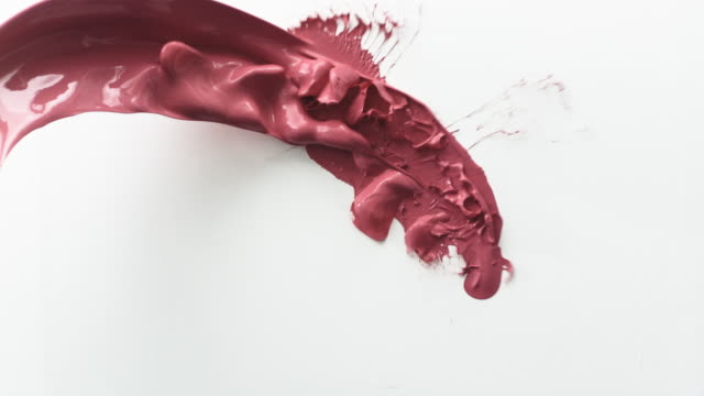 cu slo mo shot of red paint is thrown against blank wall / united kingdom - liquid stock videos & royalty-free footage