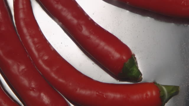 ecu slo mo shot of red pepper drifts in water / toronto, ontario, canada  - peperone video stock e b–roll