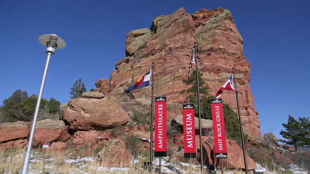 WS POV Shot of Red rocks signs to amphitheater and museum with flags and red rocks in background / Denver, Colorado, United States