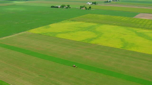 vídeos y material grabado en eventos de stock de ws aerial td ds shot of red tractor harvesting on farm in saginaw county / michigan, united state - paisaje mosaico