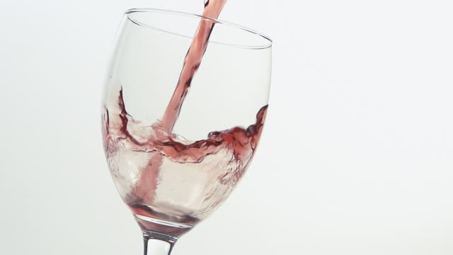 CU SLO MO Shot of Red wine being pour into glass against white background / Calvados, Normandy, France