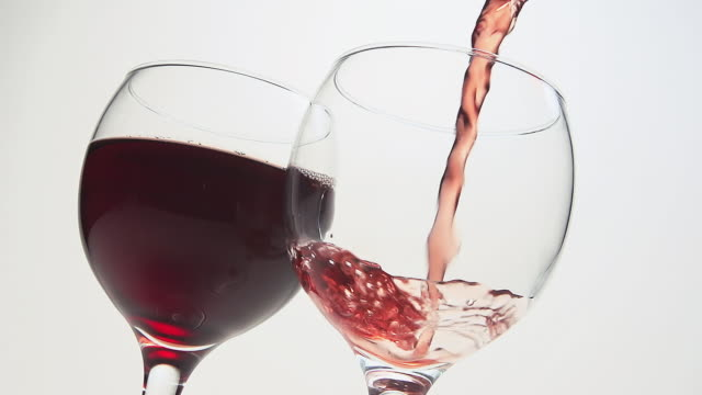 cu slo mo shot of red wine being pour into glass against white background / calvados, normandy, france - calvados stock videos and b-roll footage