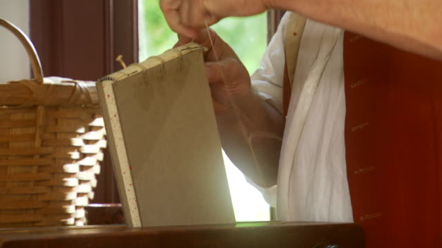 cu zo shot of reenactment  book binder sews  pages of book together during colonial times / williamsburg, virginia, united states - colonial reenactment stock videos & royalty-free footage