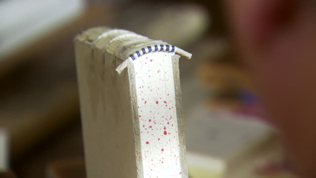 CU PAN R/F Shot of REENACTMENT  book with glue on its spine to book binder sewing  pages of  book together / Williamsburg, Virginia, United States