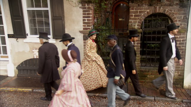 vídeos de stock e filmes b-roll de ms ha shot of reenactment group of people walking down street tilt hats towards camera and continue walking / charleston, south carolina, united states  - exército da união