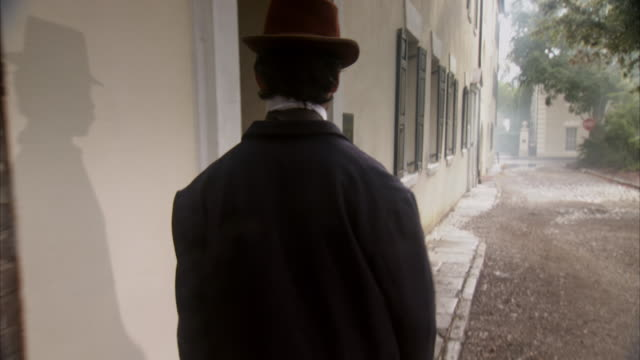 MS POV Shot of REENACTMENT John Wilkes Booth walking down the street and enters building