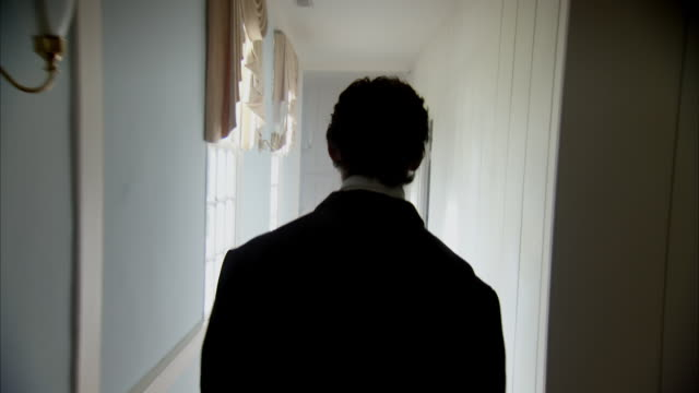 MS POV Shot of REENACTMENT John Wilkes Booth walks down hallway / United States