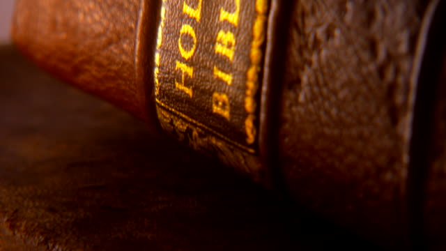 ECU TU Shot of REENACTMENT  light flickers and reflects off words HOLY BIBLE written in gold on  spine of book / Falls Church, Virginia, United States