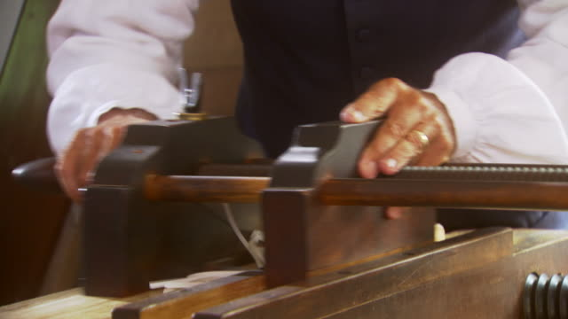 ms td shot of reenactment man operates paper cutter during colonial times / williamsburg, virginia, united states - druckmaschine stock-videos und b-roll-filmmaterial