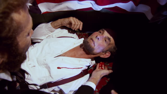 CU ZO ZI Shot of REENACTMENT man places cloth behind bloody head of President Abraham Lincoln after being shot at Fords Theatre / United States