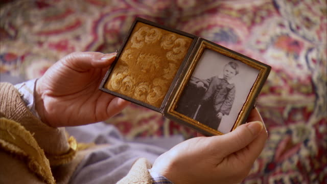 CU TS Shot of REENACTMENT Mary Todd Lincoln holding photo of Eddie Lincoln and bringing it to her chest / United States