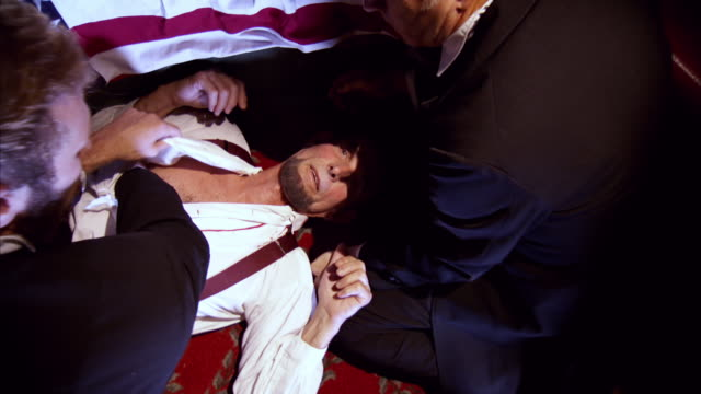MS HA ZI Shot of REENACTMENT men checking body and eyes of President Abraham Lincoln on floor after being shot by John Wilkes Booth at Fords Theatre / United States