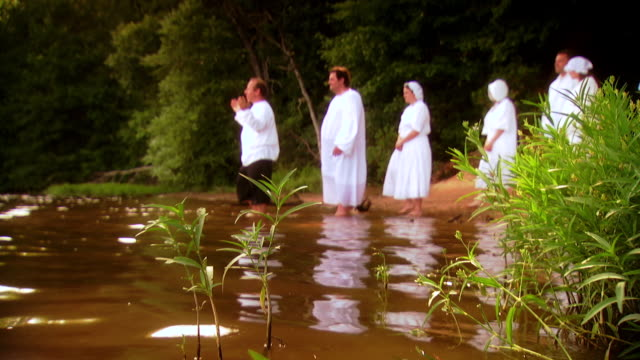 MS Shot of REENACTMENT Pastor welcomes and leads  line of people dressed in white to walk into  lake during baptism ceremony   / Fairfax Station, Virginia, United States