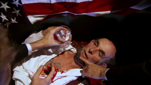 CU ZI Shot of REENACTMENT pouring water from cup into President Abraham Lincoln's mouth immediately after he is shot at Fords Theatre / United States
