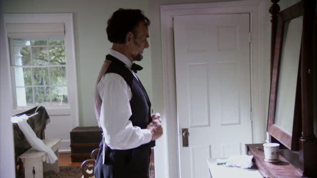 ms shot of reenactment president abraham lincoln buttoning his vest and putting on coat in bedroom / united states - エイブラハム・リンカーン点の映像素材/bロール