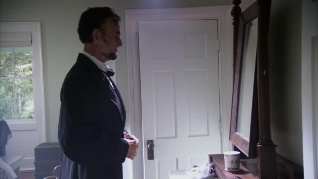 ms shot of reenactment president abraham lincoln putting on coat and leaving bedroom - お手洗い点の映像素材/bロール