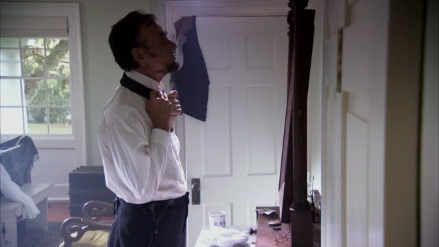 MS POV Shot of REENACTMENT President Abraham Lincoln tying his tie around neck in bedroom / United States