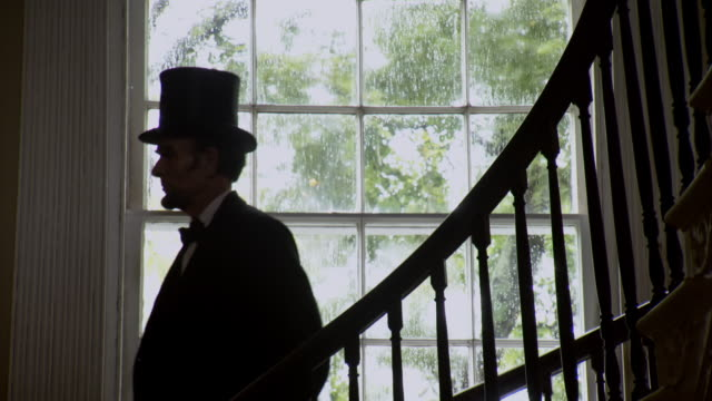 MA TD Shot of REENACTMENT President Abraham Lincoln walks down stairs and puts on his hat / United States