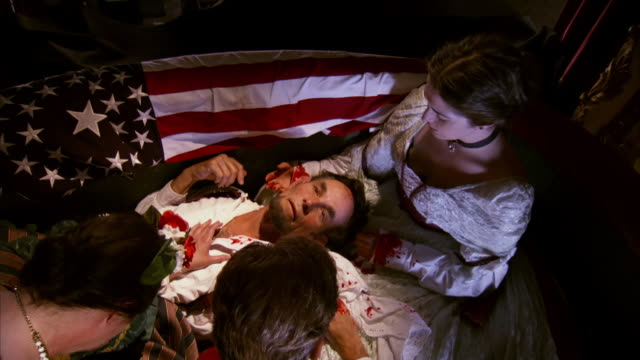MS ZI Shot of REENACTMENT red drape to reveal President Abraham Lincoln and Mary Todd Lincoln and others on floor after being shot at Fords Theatre