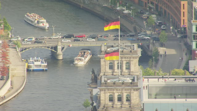 ms aerial pan shot of reichstag building and ferry passing down under bridge / berlin, germany - german flag stock videos & royalty-free footage