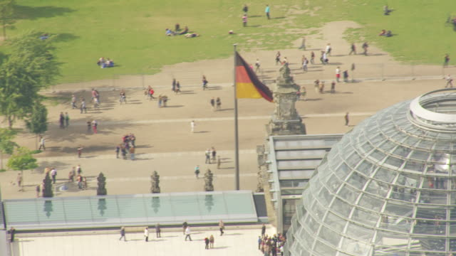 cu aerial shot of reichstag building dome and flag waving with wind / berlin, germany - cupola video stock e b–roll