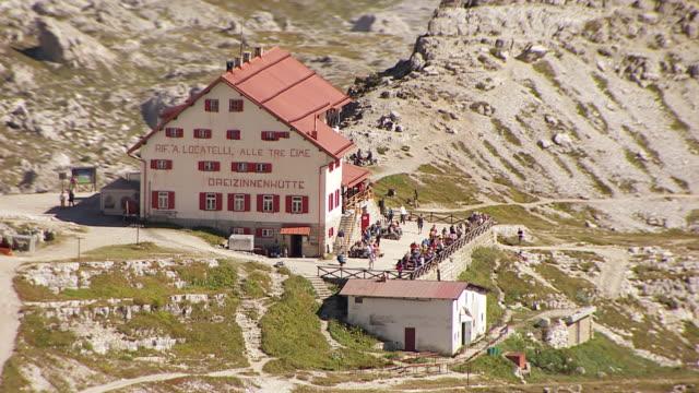 ms aerial zo shot of restaurant on top of three peaks of lavaredo in sexten dolomites / drei zinnen, belluno sudtirol - western script stock videos & royalty-free footage