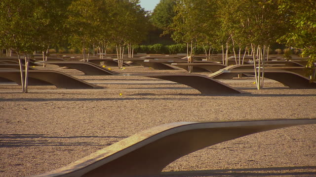 MS R/F PAN Shot of reveal September 11th memorial with trees and cement benches outside Pentagon building / Arlington, Virginia, United States