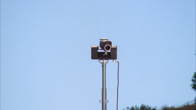 ms zi zo shot of revolving video security camera on top of a tall (maybe 25') iron pole  - big brother orwellian concept stock videos & royalty-free footage