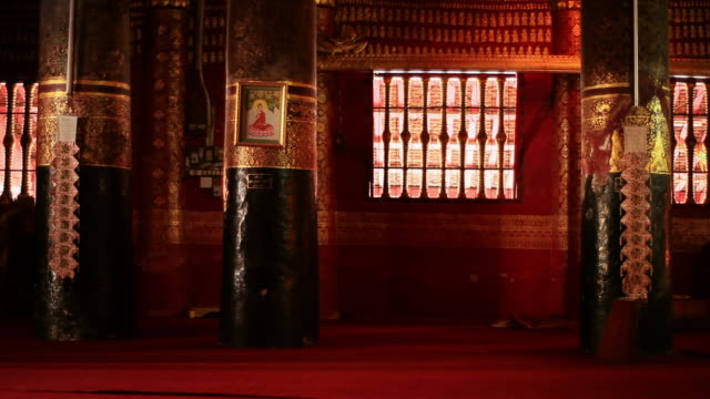 MS Shot of richly decorated dark red and gold interior of Buddhist temple with man walking away / Luang Prabang, Laos