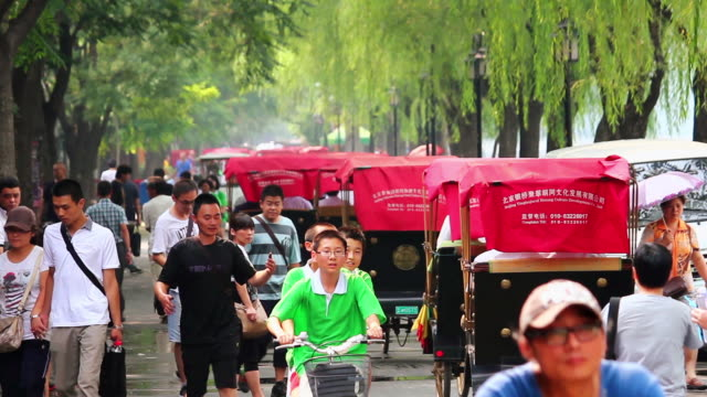 ms shot of rickshaw and people walking near houhai lakes area / beijing, china - risciò video stock e b–roll