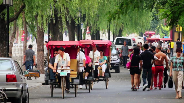 ms shot of rickshaw drivers taking tourists on tour of houhai lakes area / beijing, china - risciò video stock e b–roll