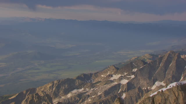 MS AERIAL TU TS Shot of Ridge with snow and pull out to orbit peak of Gran Teton and valley in background / Wyoming, United States