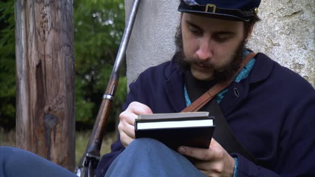ms zi shot of rifle sitting next to union soldier writing letter / middleburg, virginia, united states - unionsarmén bildbanksvideor och videomaterial från bakom kulisserna