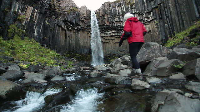 ms shot of river below svartifoss waterfalls, hanging hexagonal basalt columns underlying and young woman walking up to falls and taking photo / skaftafell national park, austur-skaftafellssysla, iceland   - newoutdoors stock videos & royalty-free footage