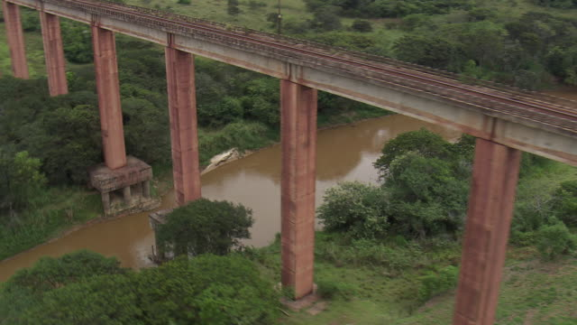 ms aerial shot of river crossing railway bridge / minas gerais, brazil - minas stock videos and b-roll footage