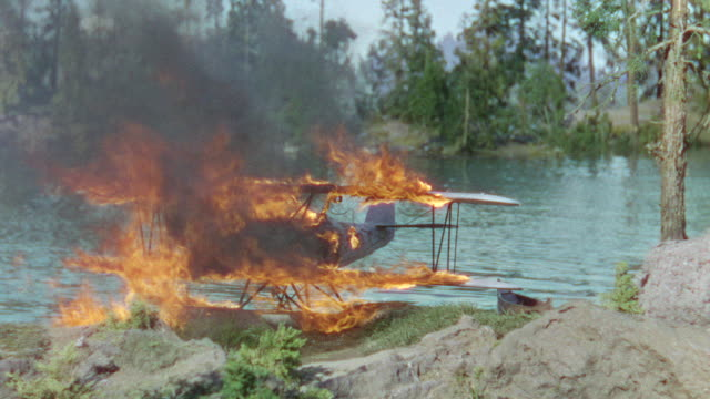 ms shot of river to forest with biplane on fire (miniature) - 複葉機点の映像素材/bロール