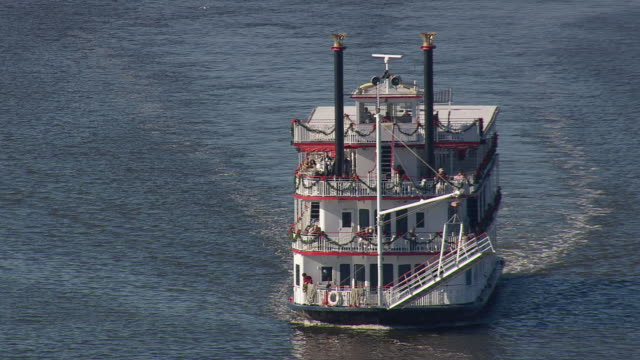 MS AERIAL ZO Shot of Riverboat Georgia Queen moving in river and cars moving on bridge / Georgia, United States