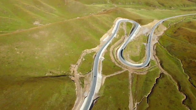 AERIAL shot of Road extending into distant horizon on grassland,Gansu,China.