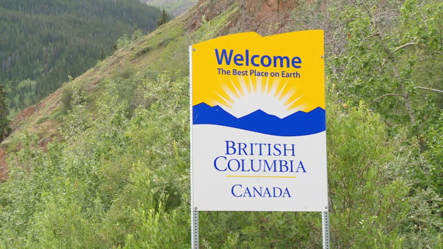 CU Shot of Road sign for British Columbia The Best Place on Earth, on Haines Highway and forest mountains behind, Yukon and British Columbia border / Yukon/British Columbia, Canada