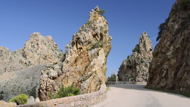 ms shot of road through the fantastic rock landscape of the calanche of piana, unesco world heritage site / gulf of porto, corsica, france - ピアナ点の映像素材/bロール