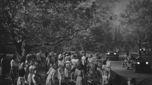ms shot of road throught forest or park as military convoy passess through and group of people stand on side of road waving to soldiers - military parade stock videos and b-roll footage