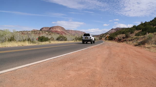 WS POV Shot of road with SUV driving past / Santa Fe, New Mexico, United States