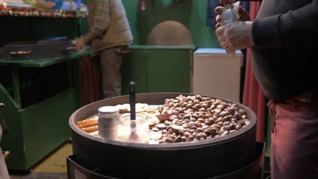 shot of roasted chestnuts stall on market stall on rathausplatz at christmas, vienna, austria, europe - marrone video stock e b–roll