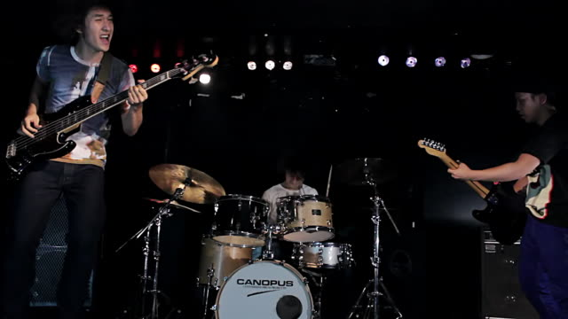 ms pan shot of rock band performing / shinjuku, tokyo, japan - bass guitar stock videos and b-roll footage
