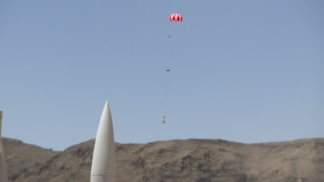 WS TS Shot of rocket with its parachute deploying lands during BALLS Experimental Rocket Launch at desert / Black Rock, Nevada, United States