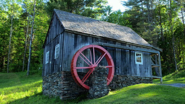 MS Shot of Rockingham Vermont old barn mill with paddle wheel red in woods / Rockingham, Vermont, United States