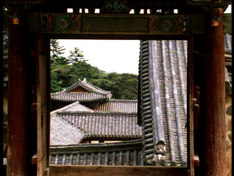 vidéos et rushes de shot of roofs and trees through open window shutters of buddhist temple tilt up to pantile roof and grey sky above - coréen