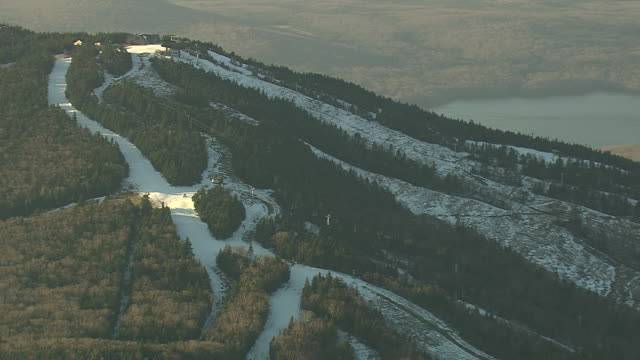 MS AERIAL DS Shot of ropeway station on topm of snow mountain / Vermont, United States