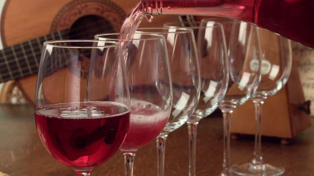 vídeos de stock e filmes b-roll de cu shot of rose wine pouring in glasses - copo de vinho