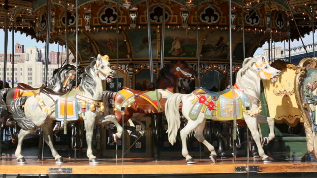 ms pan shot of rotating jane's carousel at bridge park manhattan bridge / brooklyn, new york, united states  - 回転遊具点の映像素材/bロール